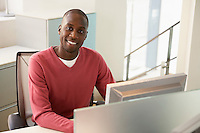 Mid-adult male office worker working at desk portrait