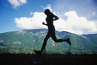 Silouhette of fit young man trail running in the mountains.  Washington Cascades, USA<br />
