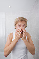 Portrait of man checking for wrinkles on his face in bathroom