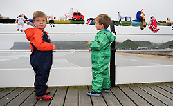 © Licensed to London News Pictures. <br /> 24/05/2014. <br /> <br /> Saltburn, United Kingdom.<br /> <br /> Bradley Smith (L), 3, and his twin brother Charlie from Doncaster enjoy the World Cup themed knitted figures that appeared over night on Saltburn pier.<br /> <br /> The Saltburn Yarn Stormers, a secret group of knitters based around the town have struck once again and produced their latest work in the build up to the World Cup by creating knitted figures representing the countries taking part in the World Cup in Brazil later in the year.<br /> <br /> The identities of the group members which remains a secret launched their most recent creation in the early hours to avoid possible detection and secretly gathered to attach the figures to the railings on the Victorian pier in the town before melting away back in to the shadows.<br /> <br /> Photo credit : Ian Forsyth/LNP