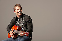 Man sitting Playing Guitar smiling