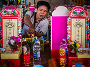 18 SEPTEMBER 2017 - BANGKOK, THAILAND: A woman sets up her family altar at Wat Mangkon Kamalawat, a Chinese temple in Bangkok, during a service to mark the last day Hungry Ghost Month. The Ghost Festival, also known as the Hungry Ghost Festival, Zhongyuan Festival or Yulan Festival is a traditional Buddhist and Taoist festival held in Asian countries. According to the Chinese calendar (a lunisolar calendar), the Ghost Festival is on the 15th night of the seventh month. In Chinese culture, the fifteenth day of the seventh month in the lunar calendar is called Ghost Day and the seventh month in general is regarded as the Ghost Month, in which ghosts and spirits, including those of the deceased ancestors, come out from the lower realm. Distinct from both the Qingming Festival (in spring) and Double Ninth Festival (in autumn) in which living descendants pay homage to their deceased ancestors, during Ghost Festival, the deceased are believed to visit the living.     PHOTO BY JACK KURTZ