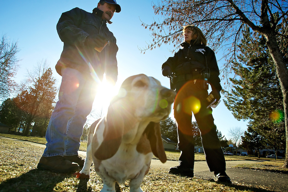 Laurie Deus, an animal control officer for the City of Coeur d'Alene, talks with Richard Davis at the Central Bark Dog Park during her afternoon rounds Monday. The city is proposing increases in fees dealing with dog licensing, impound fees and the board appeals process.