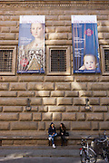 Agnolo de Cosimo Bronzino's exibition posters over modern Italian women in Piazza Strozzi..Agnolo de Cosimo Bronzino's painting of the Medici Eleanora of Toledo and son Giovanni C1545. Eleonora di Toledo (1522 - 1562), the daughter of Don Pedro Álvarez de Toledo, the Spanish viceroy of Naples. Her face is still familiar to many because of her solemn and distant portraits by Agnolo Bronzino. She provided the Medici with the Pitti Palace  and seven sons to ensure male succession and four daughters to connect the Medici with noble and ruling houses in Italy. She was a patron of the new Jesuit order, and her private chapel in the Palazzo Vecchio  was decorated by Bronzino, who had originally arrived in Florence to provide festive decor for her wedding. She died, with her sons Giovanni and Garzia, in 1562, when she was only forty; all three of them were struck down by malaria while traveling to Pisa..