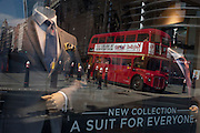 Menswear suits on sale in a retailer's window, with reflections of everyday City life and red London bus on Cannon Street in the City of London, UK.