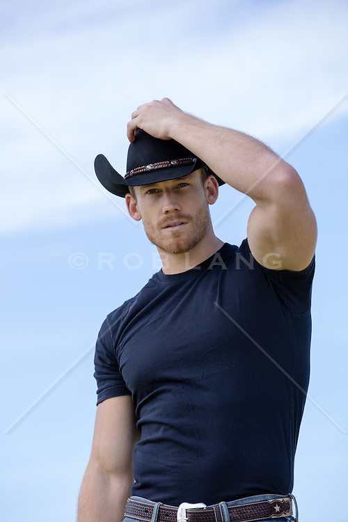 cowboy with his hand on cowboy hat