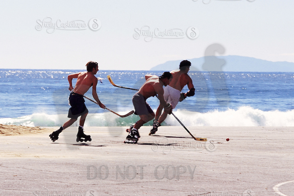 1997:  Pacific  Beach Hockey Association PBHA players skate along the asphalt with a hockey ball on inline skates as the waves break near the sand and Catlina Island is in the background.  Southern California summer sport. Transparency slide scan. Randy Moffett. Terry Glynn.