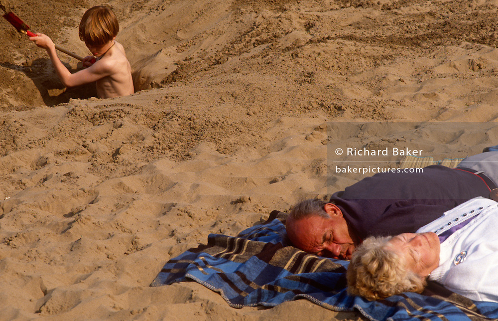 A middle-aged couple sleep on a blanket as a young boy digs a hole on the sandy beach at Scarborough. The generation gap is shown here with the older people unconscious after a day in sea air while the lad with the energy of youth puts much effort into shovelling sand from the growing hole. If they are related, they are oblivious as to the dangers of excavating holes on tidal beaches.
