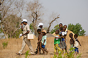 Children follow a community nurse during a national polio vaccination exercise in the village of Gbulahabila, northern Ghana on Wednesday March 25, 2009.