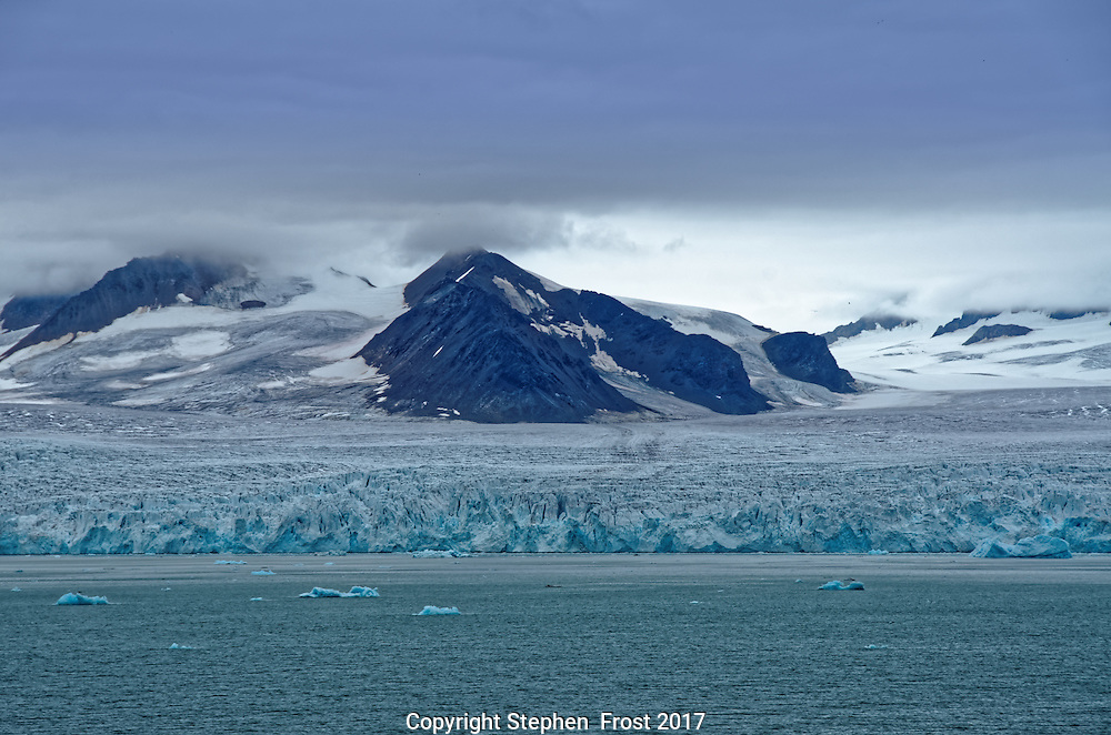Glacier in Svalbard, with small floating icebergs.<br />