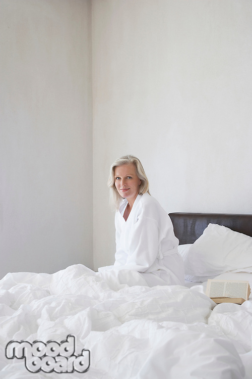 Mature woman in bathrobe sitting up in bed smiling next to open book side view