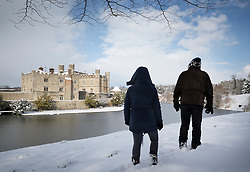 © Licensed to London News Pictures. 27/02/2018. Leeds Castle, UK. Walkers pass Leeds Castle after heavy snow has closed it for the day. Freezing temperatures and heavy snow are affecting large parts of Kent.  Photo credit: Peter Macdiarmid/LNP