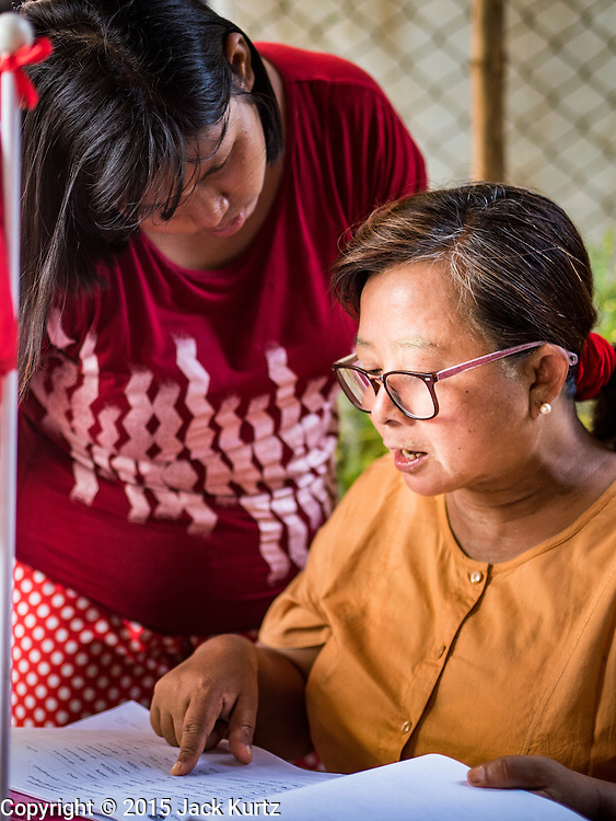 02 NOVEMBER 2015 - YANGON, MYANMAR: A Burmese voter (left) looks for her name on a list of voters with the help of a NLD outreach worker at a NLD campaign outreach office in North Okkalapa, a township in Yangon. Voter registration rolls were released Monday. Voters and party officials are double checking rolls to ensure accuracy.  National elections are scheduled for Sunday Nov. 8. The two principal parties are the National League for Democracy (NLD), the party of democracy icon and Nobel Peace Prize winner Aung San Suu Kyi, and the ruling Union Solidarity and Development Party (USDP), led by incumbent President Thein Sein. There are more than 30 parties campaigning for national and local offices.     PHOTO BY JACK KURTZ