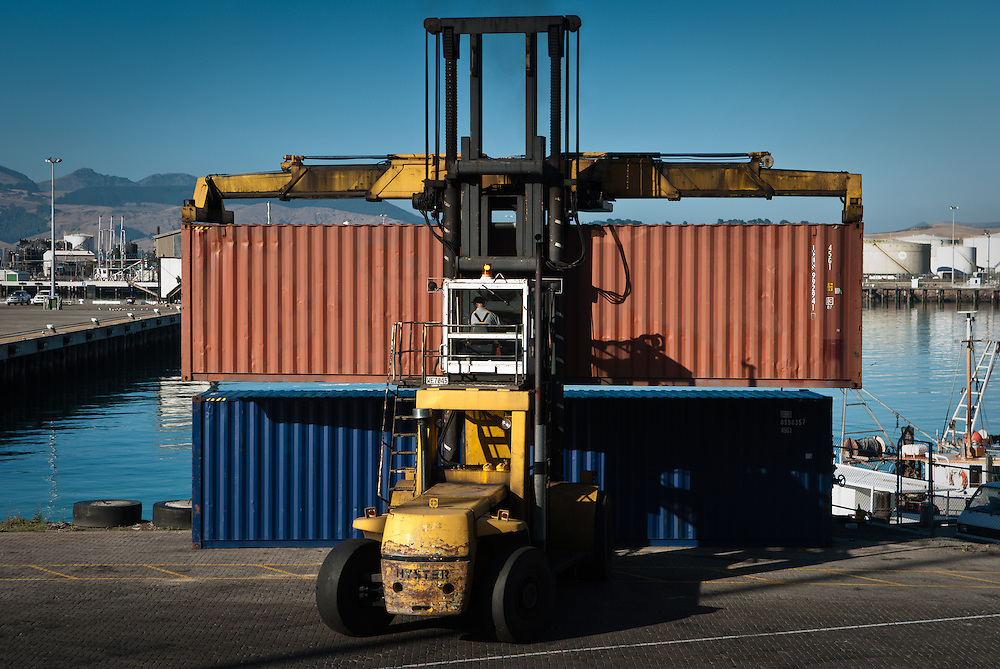 A container handler operator maneouvres a metal freight container to stack on the quayside, Lyttelton, New Zealand