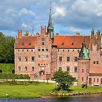 History and Design of Egeskov Castle in Kv&aelig;rndrup, Denmark <br /> During the mid-16th century, Denmark was plagued by civil wars plus political and religious upheaval.  Therefore, it was common for Dutch noblemen like Frands Brockenhuus to build a fortress to defend their estate and family from attacks.  The design of the Egeskov Slot included a wide moat, three foot walls, battlements, arrow slits plus machicolations for dropping stones or scalding oil from the towers onto attackers below.