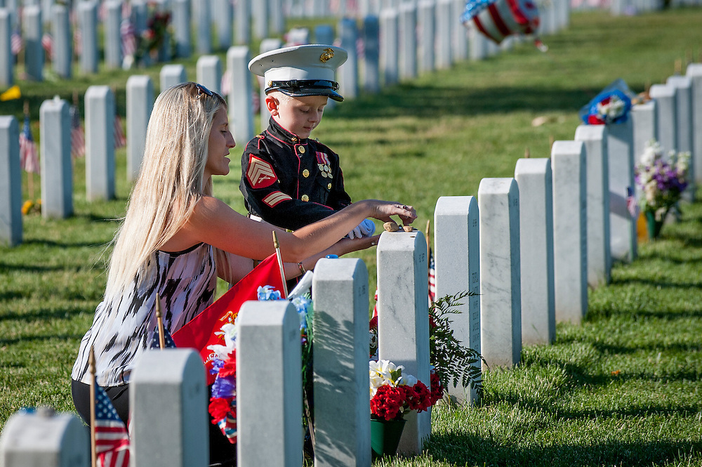 On Memorial Day, Brittany Jacobs of Hertford, North Carolina and her son, Christian, 4 tend to the headstone of her husband, Marine Sgt. Christopher Jacobs, in Section 60 at Arlington National Cemetery in Arlington, Virginia, USA, on 25 May 2015.