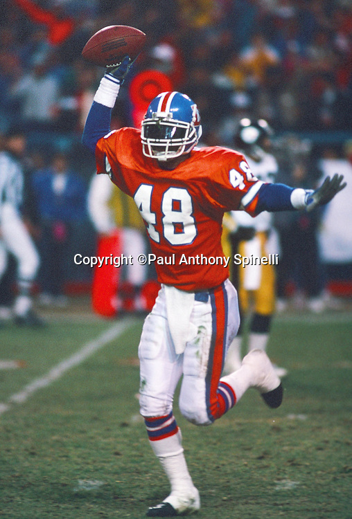 Denver Broncos cornerback Randy Robbins (48) holds the ball in the air as he runs off the field in celebration after a turnover during the NFL AFC Divisional playoff football game against the Pittsburgh Steelers on Jan. 7, 1990 in Denver. The Broncos won the game 24-23. (©Paul Anthony Spinelli)