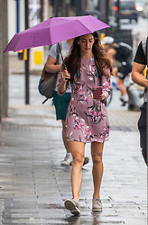 © Licensed to London News Pictures. 13/08/2020. London, UK. Commuters in Putney in South West London were caught with rain this morning after several days of dry hot weather as a tropical heatwave hit the South East of England which saw temperatures in excess of 35c ... The Met Office have issuing a yellow weather warning for thunderstorms and heavy rain for the London area with risk of flooding and possible travel disruption. Photo credit: Alex Lentati/LNP