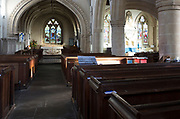 View past wooden pews through chancel arch to sanctuary and altar inside the church at Urchfont, Wiltshire, England, UK