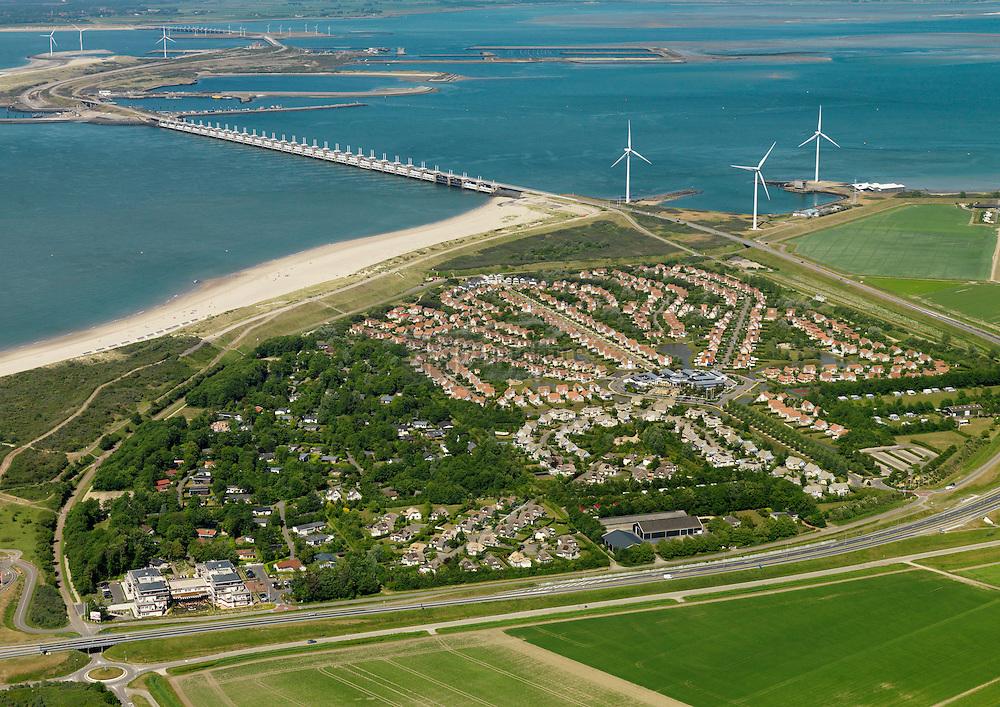 Bungalowpark de Banjaard aan de Noordzee met op de achtergrond stormvloedkering en Oosterschelde