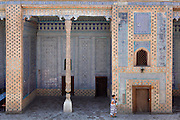 View from above of a woman walking in the Harem of the Tash Khauli Palace, 1830-38, Khiva, Uzbekistan, pictured on July 6 2010, in the summer morning light. The courtyard is decorated with patterned blue and white tiles set in brick. Commissioned by Allah Kuli Khan the Tash Kauli palace is a huge complex containing 163 rooms which took its architects, Tajiddin and Kalandar, 10 years to build. The harem, occupying about half of the palace has 5 aiwan terraces, with delicately carved wooden pillars,  behind which were the quarters for the khan and his wives. Across the courtyard were the  concubines' apartments.  The facades and walls around the courtyards were decorated with traditional blue, ultramarine and white colours majolica made by Abdullah.