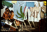 Three boys clown around beside towels drying on line on front porch of home in Eirunepe, AM. Brazil