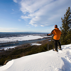 A man snowshoes above the Connecticut River Valley in Hadley, Massachusetts.  Mount Holyoke in Skinner State Park.  Metacomet-Monadnock Trail. New England Trail