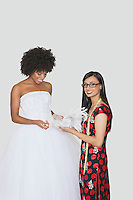 Portrait of Indian female designer assisting African American bride with feather fascinator over gray background