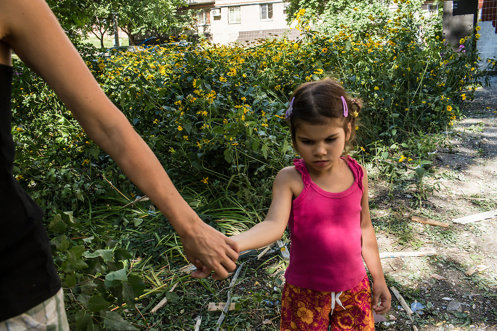 A young girl who lives in a neighboring apartment to those destroyed by a suspected grad rocket strike on Tuesday, July 29, 2014 in Donetsk, Ukraine.