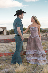 cowboy and a woman in a long prairie dress on a ranch