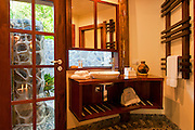 Bathroom and outdoor shower in bure guest room at Matangi Private Island Resort, Fiji.