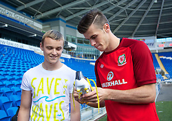 CARDIFF, WALES - Monday, September 9, 2013: Wales' Gareth Bale signs a boot for supporter Scott Abbruzzesse after a training session at the Cardiff CIty Stadium ahead of the 2014 FIFA World Cup Brazil Qualifying Group A match against Serbia. (Pic by David Rawcliffe/Propaganda)