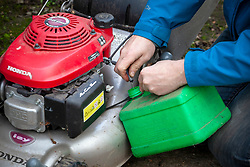 Lawnmower maintenance. Draining the petrol tank before storing over winter