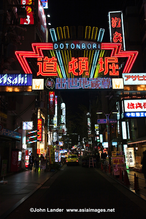 Dotombori Street running alongside the Dotonbori Canal between the Dotonboribashi Bridge and the Nipponbashi Bridge in Osaka. Dotonbori is famous for its historic theaters, its shops and restaurants and its many neon and mechanized signs, including candy manufacturer Glico giant electronic display of a runner crossing the finish line, moving giant crabs and other dramatic kitsch.