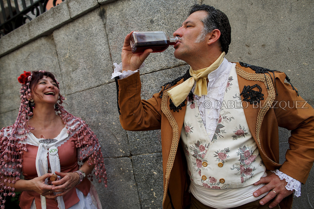 'Mayas' and 'Mayos' drink wine as they cerebrate the 'La Maya' tradition in the streets around the San Lorenzo church on May 10, 2015 in Lavapies neighborhood, Madrid, Spain. 'La Maya' festivity is a pagan tradition to celebrate the beginning of the spring which is believed to come from the medieval age. In old times the 'Maya's Festival' used to take place at The 'Mayas' field' (Prado de las Mayas) which is where now the San Lorenzo church is located. La Maya combines symbols of fertility and prosperity on agriculture and shepherding economy. A 'Maya' girl dressed with traditional customs sits on an altar in the street decorated with flowers, plants and cushions. Other Mayas and Mayos offer flowers, traditional sweets, lemonade, and wine to members of the public as they play music and dance. (© Pablo Blazquez)