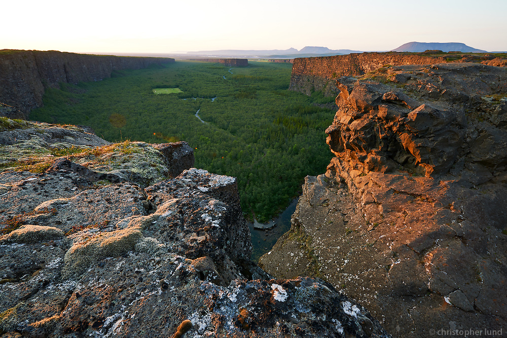 Ásbyrgi canyon late evening. Ásbyrgi was most likely formed by two catastrophic glacial flooding of the river Jökulsá á Fjöllum after the last Ice Age, first 8-10,000 years ago, and then again some 3,000 years ago. The canyon's steep sides are formed by cliffs up to 100 metres in height. Down in the canyon, visitors walk through a woodland of birch and willow. Between 1947 and 1977, a number of foreign tree species were introduced, including fir, larch and pine. The small lake Botnstjörn is home to a variety of waterfowl species. http://en.wikipedia.org/wiki/Ásbyrgi