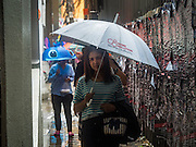 "16 SEPTEMBER 2015 - BANGKOK, THAILAND:  People with umbrellas walk along Phaya Thai Street during the rain in Bangkok. The remnants of tropical storm ""Vamco"" hit Bangkok Wednesday. The storm, downgraded to a tropical depression, brought bands of rain to central Thailand, including Bangkok. The Thai Meteorological Department said the storm would help alleviate the drought that has gripped Thailand since late last year.    PHOTO BY JACK KURTZ"