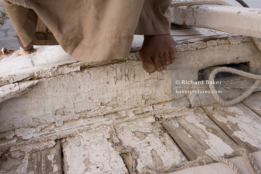 A detail of a crewman's foot with the peeling boards of his boat while sailing on the River Nile at Luxor, Nile Valley, Egypt. Feluccas are ancient Egyptian sail boats which were used in ancient times as a primary mode of transport and are the only type of boat that is still used extensively in the country.