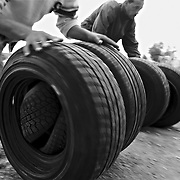 MELILLA, SPAIN - APRIL 21, 2010 : Men carrying contraband  new tires  by rotating them in order in the  border of  El Barrio Chino between Spain and Morocco on April 21 , 2010 in Melilla. Spain. Every day at the pedestrian border of El Barrio Chino hundreds of people are involved in transporting smuggled goods from Melilla a Spanish enclave on the North African coast to Morocco.For each package introduced in Morocco receive between 3 an 5 euros depending on size,with a little luck achieved make three trips a day.It is estimated that from Monday to Thursday on foot enter Melilla 8.000 porters, mostly women, to return to Morocco with huge sacks of goods from the warehouse border area of Beni Enzar in Melilla .( Photo by Jordi Cami )