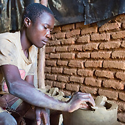 CAPTION: Alex is 20 years old. Two years ago, he shifted from building houses into stove production. He completes around 60 stoves every fortnight, and each one earns him 250 kwacha (€ 0.50). This is more than he used to earn as a builder, he says. LOCATION: Phuka Phuka Stove Production Group, Area 36, Lilongwe, Malawi. INDIVIDUAL(S) PHOTOGRAPHED: Alex Blessings.