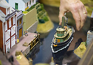 Hicksville, New York, USA. February 22, 2015. Deus ex machina. A model train club member reaches his hand down to position a model boat in an old fashioned dock scene with marine buildings displayed at the Model Train Exhibit hosted by Trainville Hobby Depot at the Broadway Mall. The person positioning the ship is the club member who built the scene. Donations were accepted at exhibit to support the Nassau County Empire State Games for the Physically Challenged.