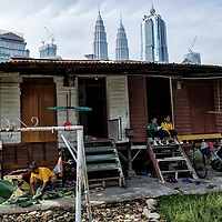 Family members of foreign workers perform their daily activities at their rented wooden houses against the background of iconic Petronas Towers in Kampung Baru, Kuala Lumpur, Malaysia, 12 April 2017.