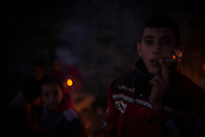 A young refugee from Syria is seen smoking paper cigarets with his friends outside the camp. Hundreds are living outside the Moria camp in a olive trees plantation. About 8500 migrants and refugees are living in hard condition on the island of Lesvos, many of them outside the organized camp. Moria, Greece. December 12th 2017.