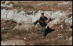A Palestinian youth carries a wounded comrade to a waiting ambulance, during a clash with Israeli soldiers in the West-bank city of Ramallah. (Photo © Jock Fistick)