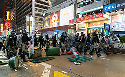 Hong Kong, China. 13th October 2019. Woman suspected of being pro-Beijing is assaulted by pro-democracy protestors in Mongkok district in Kowloon on Sunday evening. This incident was one of several throughout Hong Kong on Sunday which saw acts of vandalism carried out by a minority in the pro-democracy movement.  Riot Police move forward to clear protestors in formation on Nathan Road. Iain Masterton/Alamy Live News.