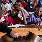 A teacher uses a model of the female genitalia to explain the procedure of FGM to the young students, some of them who will soon be facing their own rite of passage. FGM is a traditional rite of passage for girls into womanhood. FGM has many forms in Kenya, in the Loita Hills FGM involves that the girl's clitoris and inner and outer labia is cut of, an extremely painful and dangerous procedure with  lifelong medical and psychological implications. <br /> <br /> It is mainly Maasais who live in the Loita Hills up above the Serengeti plains. They live in small villages and communities called bomas and live mainly of raising and selling live stock such as cattle and goats. Its a very remote region in Kenya, hard to get to without a four wheel drive with very little infrastructure and up till 2010 no mobile phone network. The Maasais are well known though out Kenya and the world for their colorful clothing and their way of keeping their old traditions alive...The charity S.A.F.E which is a theater group also works with local partners in educating youngsters about HVI/AIDS and Female Genital Mutilation.