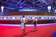 UNITED KINGDOM, London: 02 February 2016 Promotional girls walk past a wide display of gambling screens at this years ICE Totally Gaming Convention held at the Excel Arena, East London. The three day event is the world's premier international expo for gaming and gambling professionals. Rick Findler / Story Picture Agency