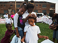 September 16, 2014 - Zacahya Craft, 7, leans on friend, Kayla Rogers, 7, as she holds her brother, Anthony Laird, 7, during a prayer led by Stanford L. Hunt, senior pastor, Salem Gilfield Baptist Church, during a peace rally sponsored by the Southern Christian Leadership Conference Memphis and Stop the Killing Movement at Foote Homes Tuesday evening. (Yalonda M. James/The Commercial Appeal)