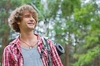 Smiling male hiker looking away in forest