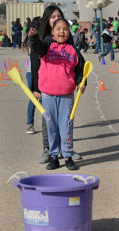 jt030317d/a sec/jim thompson/  Layla Robertson, 4th grader at Wherry Elementary School  throws a foam arrow into a bucket in one of the throwing stations at the USATF RunJumpThrow experience Friday morning in Albuquerque, NM.  Friday March 03, 2017. (Jim Thompson/Albuquerque Journal)
